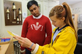 A young person in a yellow raincoat & long hair standing next to a young person wearing a red jumper. They are concentrating on a document, a map, an artwork, or instructions.