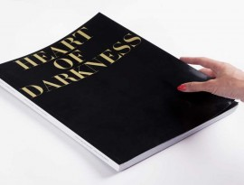 A slim hand with orange nail polish holding a large black book with large gold font reading