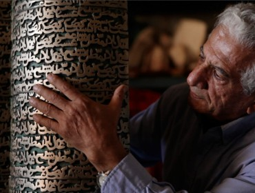 """Iranian artist Parviz Tanavoli touches his sculpture, """"Poet Turning Into Heech."""" Heech means """"nothing"""" in Persian."""