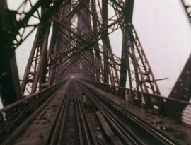 Alia Syed, Points of Departure: A dramatic film still of a muddy red railway bridge made of steel.