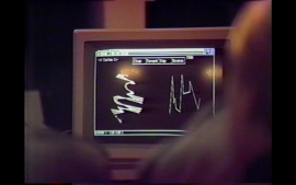 Grainy film still featuring two out of focus figures looking at a computer screen displaying indecipherable charts and lines.