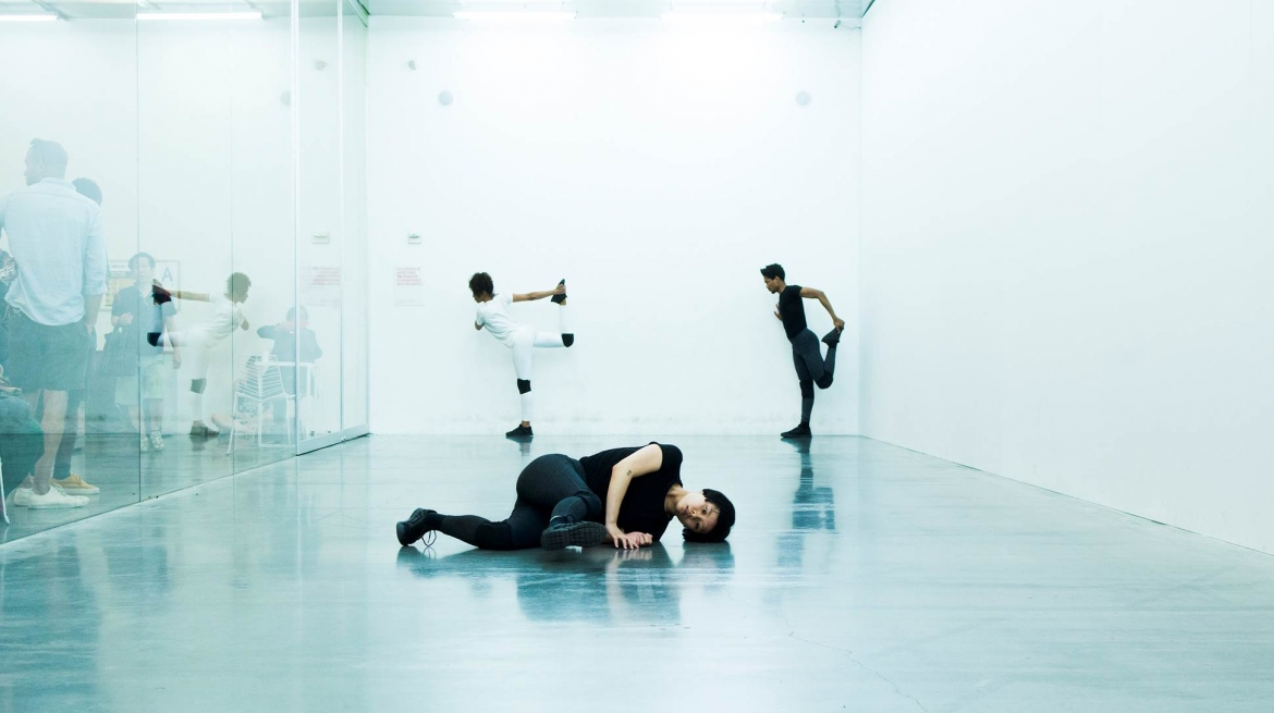 "Cally Spooner, On False Tears and Outsourcing - dancers responsible for delivering self-organized efforts to resolve difficult and time-consuming issues ""go the distance"" across multiple overlapping phases using appropriated competitive strategies and appropriated intimate gestures, 2016 dancers, acoustic panels, daylight bulbs, live radio and glass installation view New Museum, New York, 27 April - 19 June 2016 Courtesy the artist and New Museum, New York Photography Jeremiah Wilson"